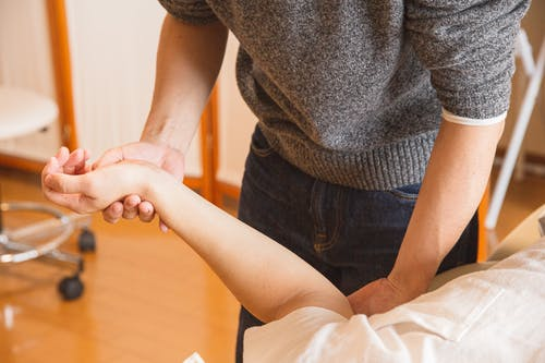 hiring an injury attorney: doctor testing a woman's elbow.