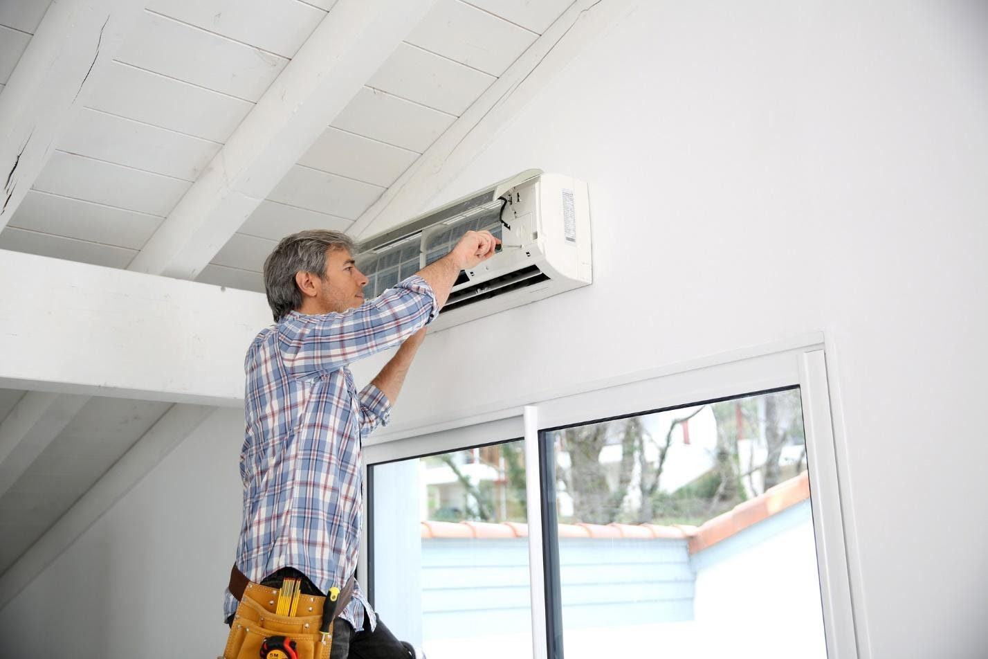 experts in air conditioning: man repairing AC unit.