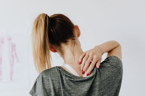 uses of CBD: woman feeling the back of her neck.