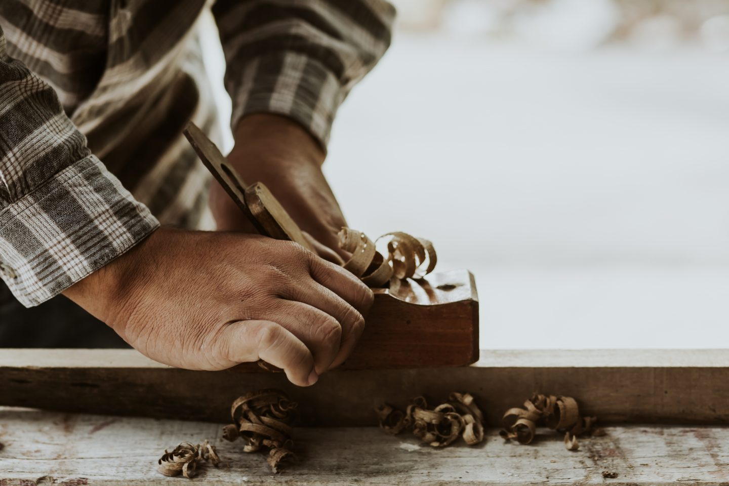 Carpenters experienced wood is using spokeshave to decorate the furniture