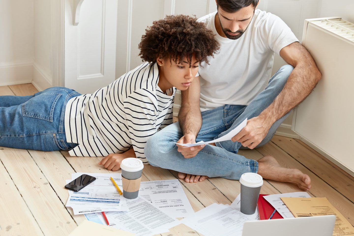Family couple maintains home accounting, discuss plans and future payments, surrounded with bills on floor, dressed in domestic clothes, drinks tasty hot coffee, analyze income chart together Things you need to do before moving in with your special someone!
