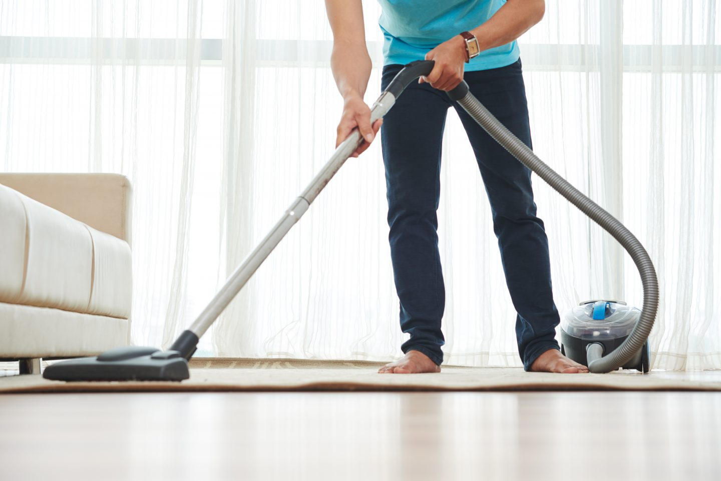 Man cleaning carpet in his room with vacuum cleaner