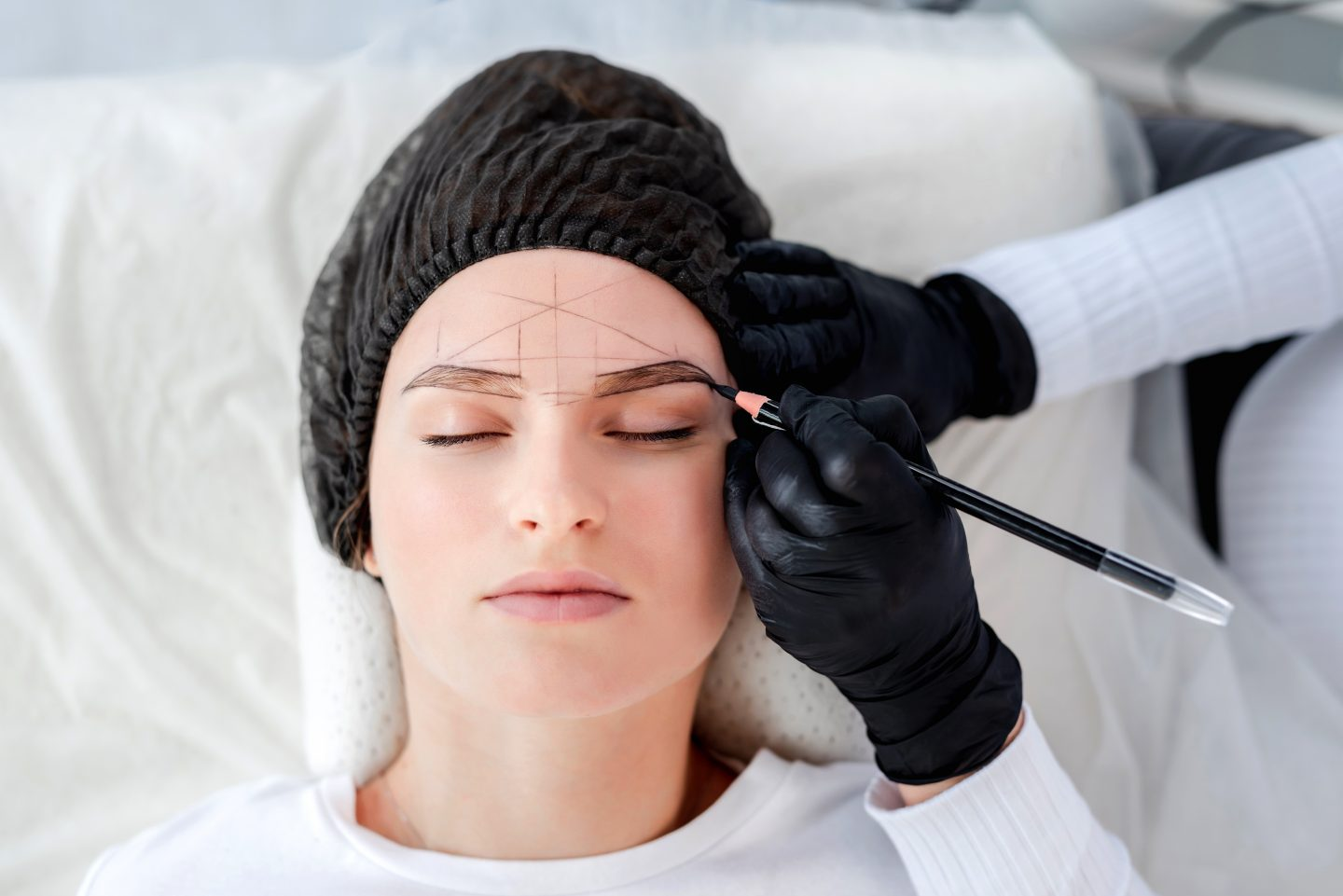 Microblading process. Beautiful girl lies while permanent makeup master draws eyebrows shape with pencil