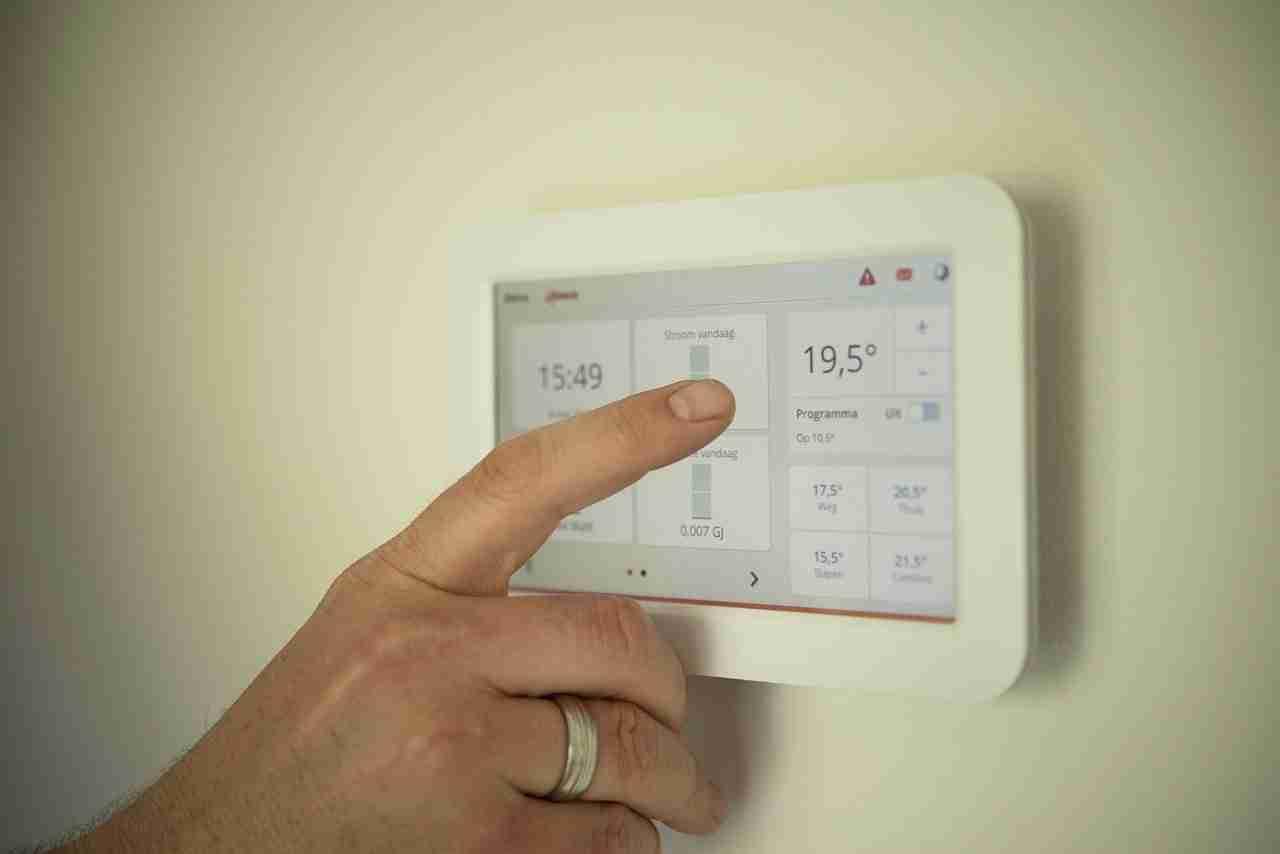 man adjusting his thermostat